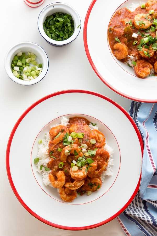 Camarones criollos sobre arroz en un tazón blanco con borde rojo