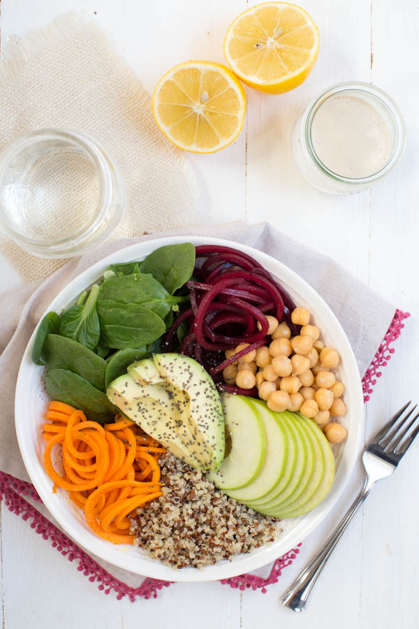 Vintage Buddha Bowl with Lemon Tahini Dressing in a White Bowl with Fork and Glasses