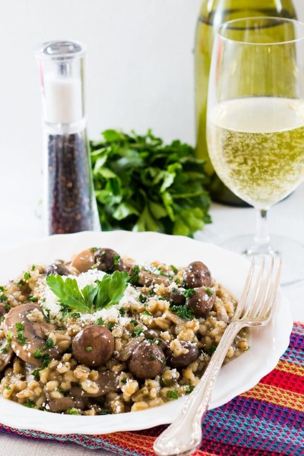 Skinny Mushroom and Barley Risotto in bowl with fork and glass of white wine