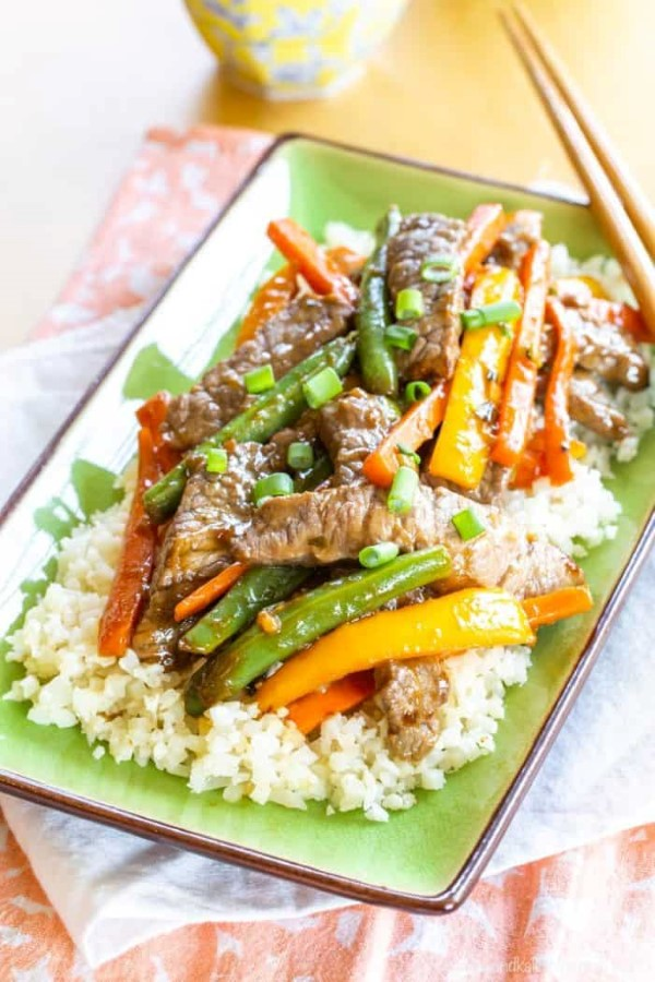 Gluten-free meat stir fry Stir fry over rice on a green tray with chopsticks