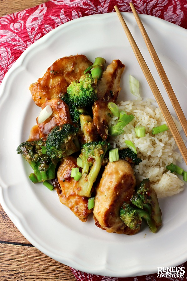Chicken and broccoli stir fry on a white plate with chopsticks