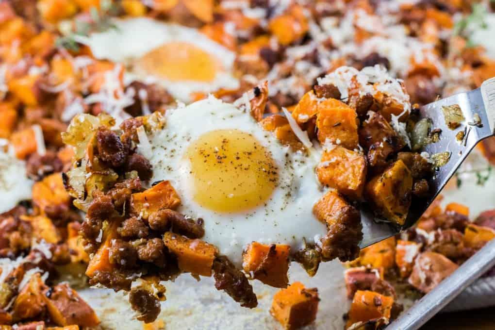 Hash de patata dulce con huevos y salchichas en una espátula tomada de una sartén