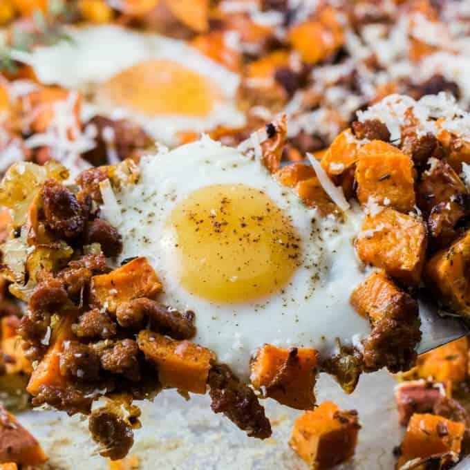 Hermoso huevo con batatas y salchichas en una espátula