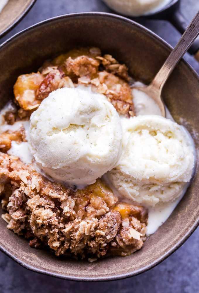 Pêssego sem glúten crocante em uma tigela com duas bolas de sorvete de baunilha.