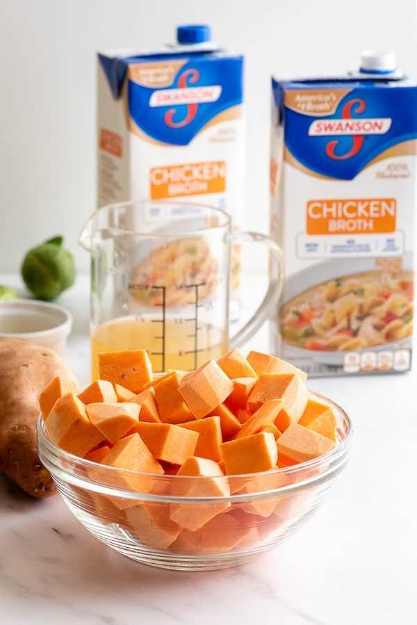 Batatas en cubos en un recipiente de vidrio y recipientes de caldo de pollo