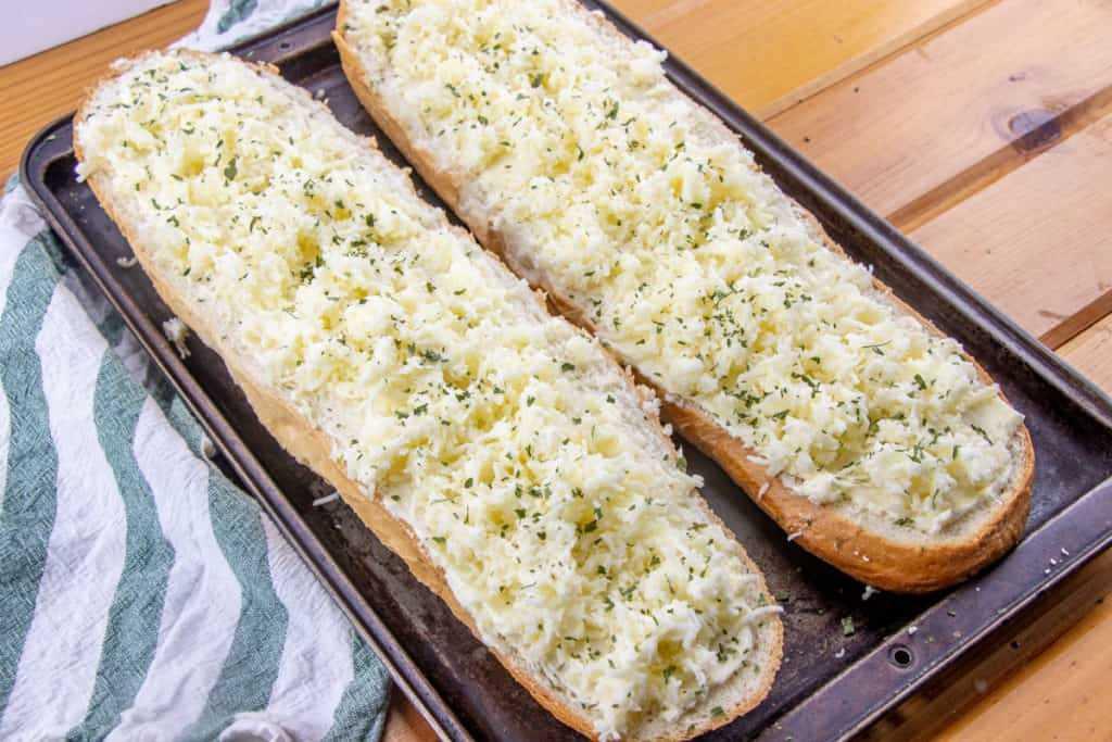 mezcla de queso y mayonesa de mozarella distribuida uniformemente sobre la mantequilla de ajo en el pan francés