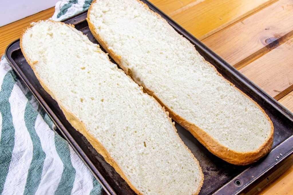 Pan francés en rodajas a la mitad en una bandeja para hornear