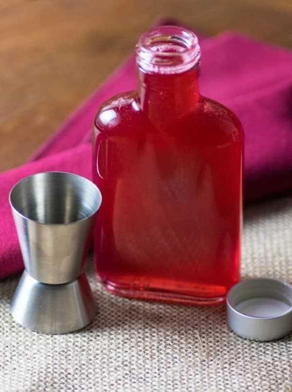Jarabe de ruibarbo en una botella con un vaso de chupito
