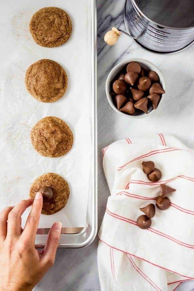 una mano presionando un beso de chocolate en una galleta