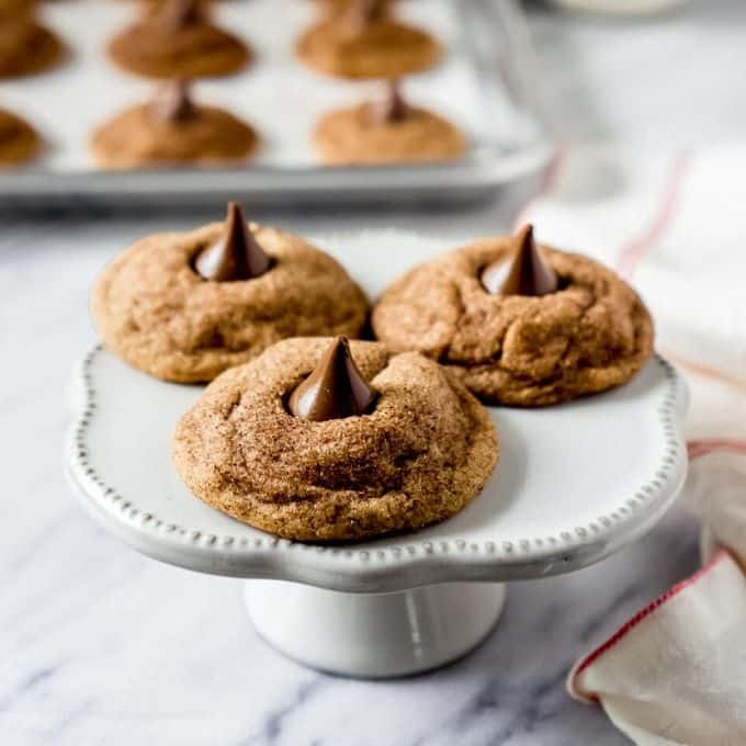 Snickerdoodle fácil Hershey Kiss Cookies en bandeja blanca con otras en el fondo en una bandeja de horno