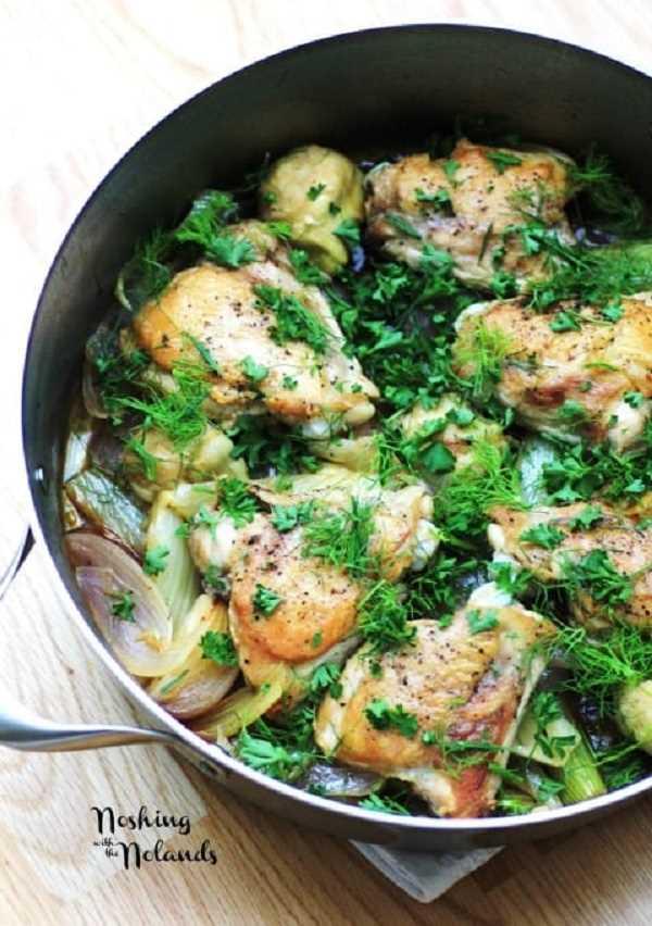 Pollo, hinojo y alcachofas en una sartén adornada con hojas de hinojo