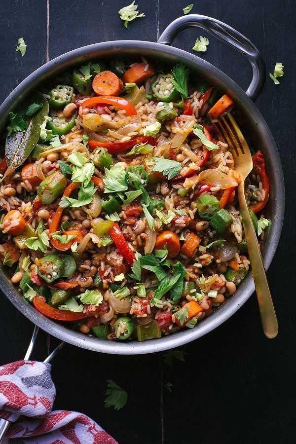 Jambalaya de verduras en una sartén con un tenedor