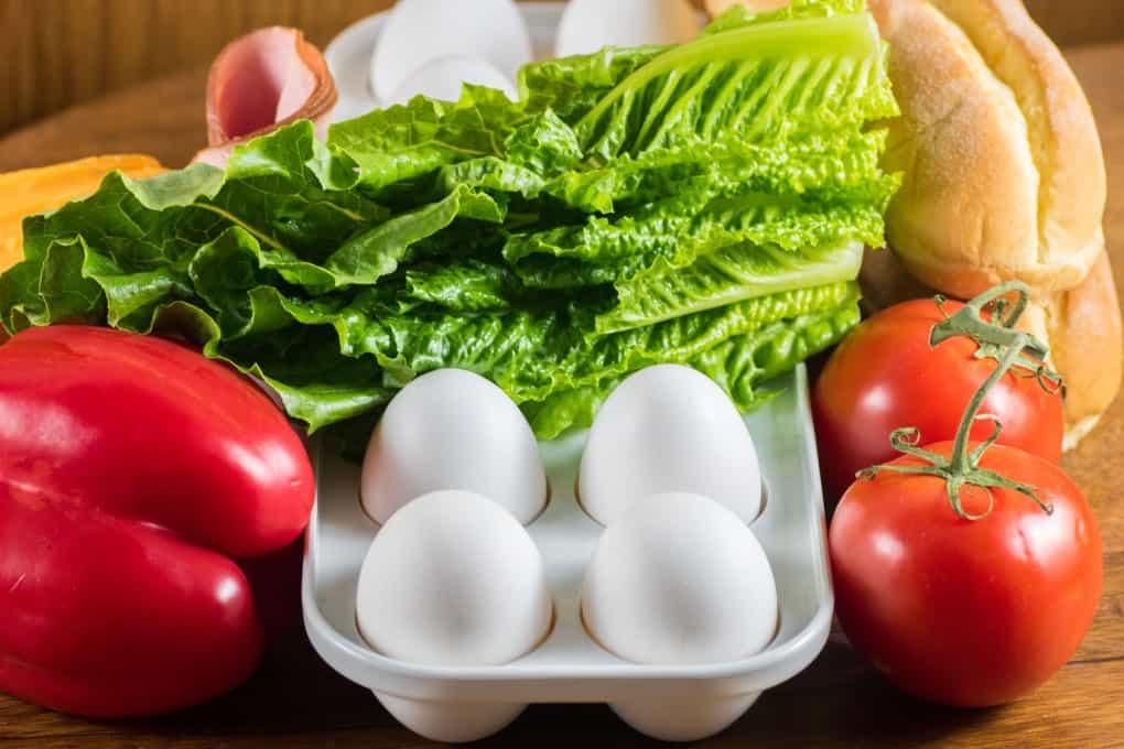 Huevos, pimientos rojos, lechuga, tomates, jamón, queso y bollos.
