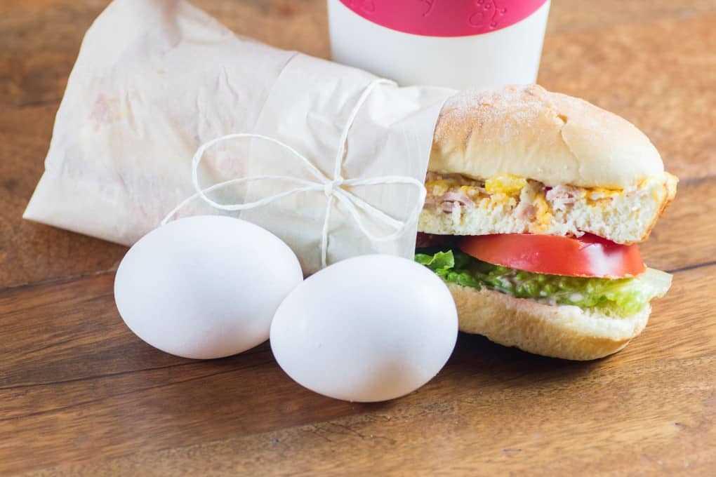 Breakfast Sandwich To Go con taza de café y dos huevos