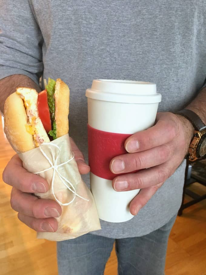 Hombre sujetando un Breakfast Sandwich To Go y una taza de café
