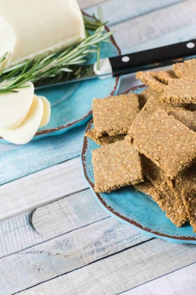 Galletas sin gluten Receta en un plato azul con queso blanco en rodajas en el fondo.