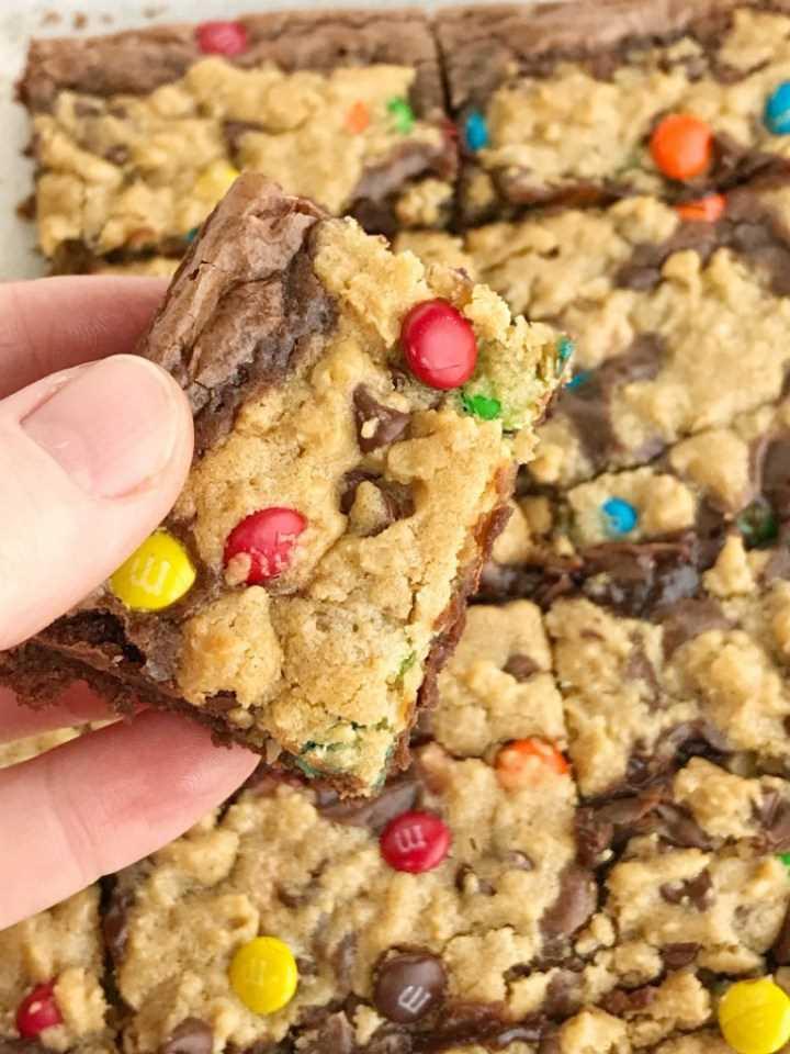 Brownies de galletas de monstruos | Cookies de monstruos | Brownies | Brookies | Los brownies de galletas monstruos comienzan con una mezcla de brownie en caja y luego se cubren con una masa de galletas monstruosas casera. ¡Dos postres en uno! Brownies de chocolate con leche y galletas monstruosas cargadas de mantequilla de maní, avena, chispas de chocolate y m & m's. #dessert #easydessertrecipes #brownies