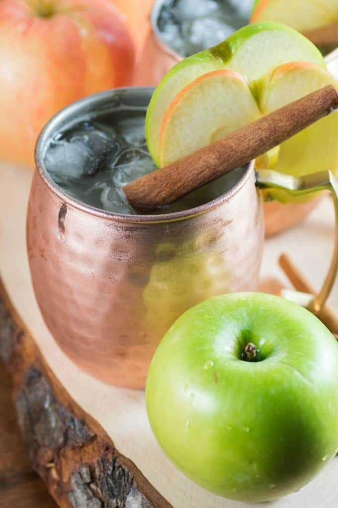 Apple Bourbon Moscow Mule en una taza de cobre con rodajas de manzana.