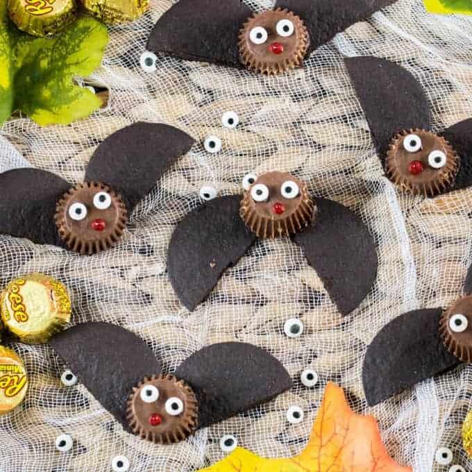 Tazas fáciles de mantequilla de maní de murciélago en una bandeja con gasa y decoraciones otoñales de hojas, Reese's y globos oculares.