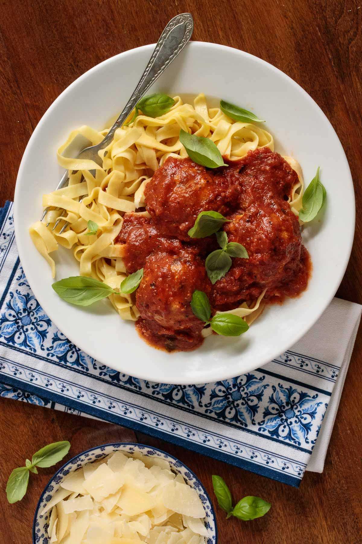 Foto de portarretrato de un tazón blanco lleno de albóndigas de pollo italiano y marinara y pasta.