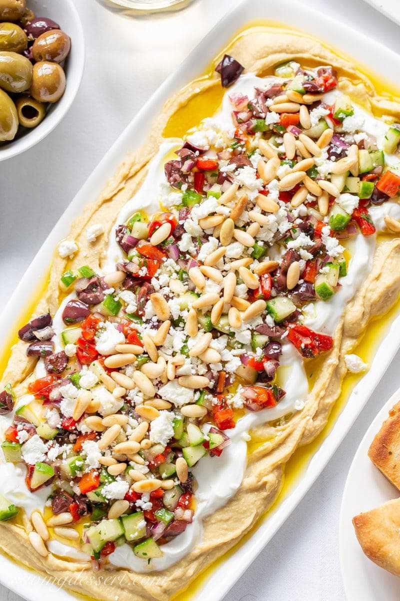 Una fuente pequeña con salsa de hummus griego en capas con yogur, pimientos rojos, pepinos, cebolla, aceitunas, queso feta y piñones
