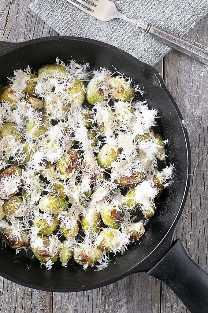 Coles de Bruselas asadas con parmesano en una sartén de hierro fundido, tiro arriba.