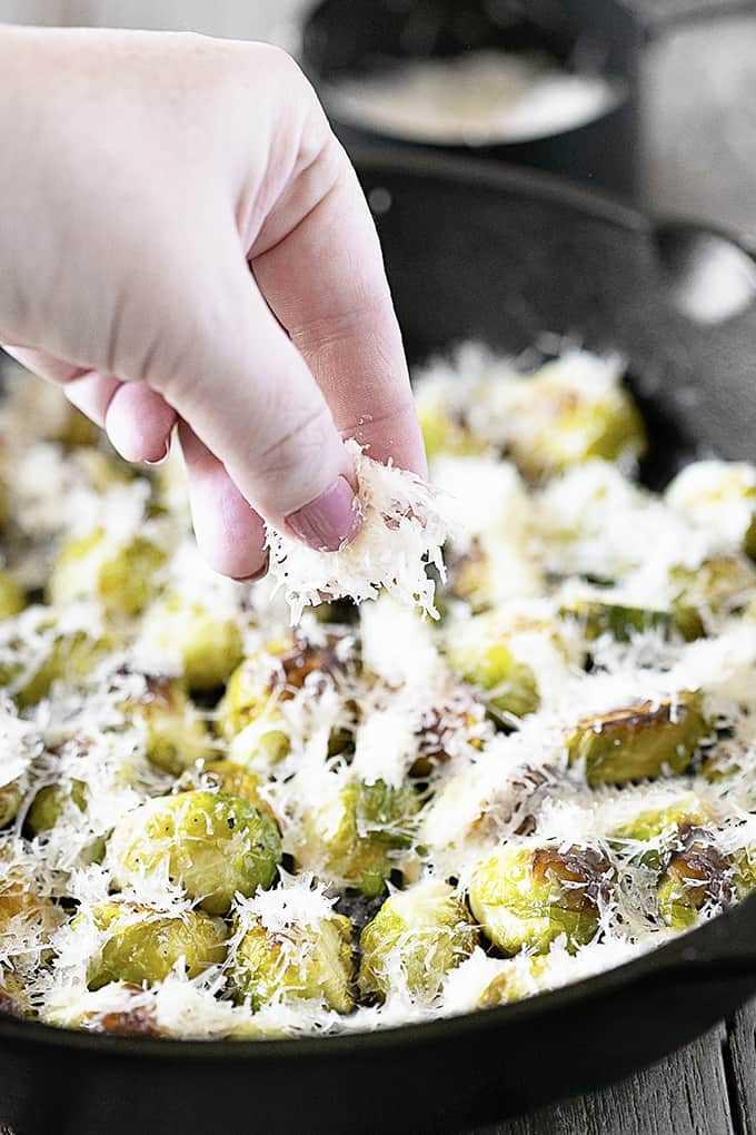 Espolvorear parmesano sobre coles de Bruselas asadas