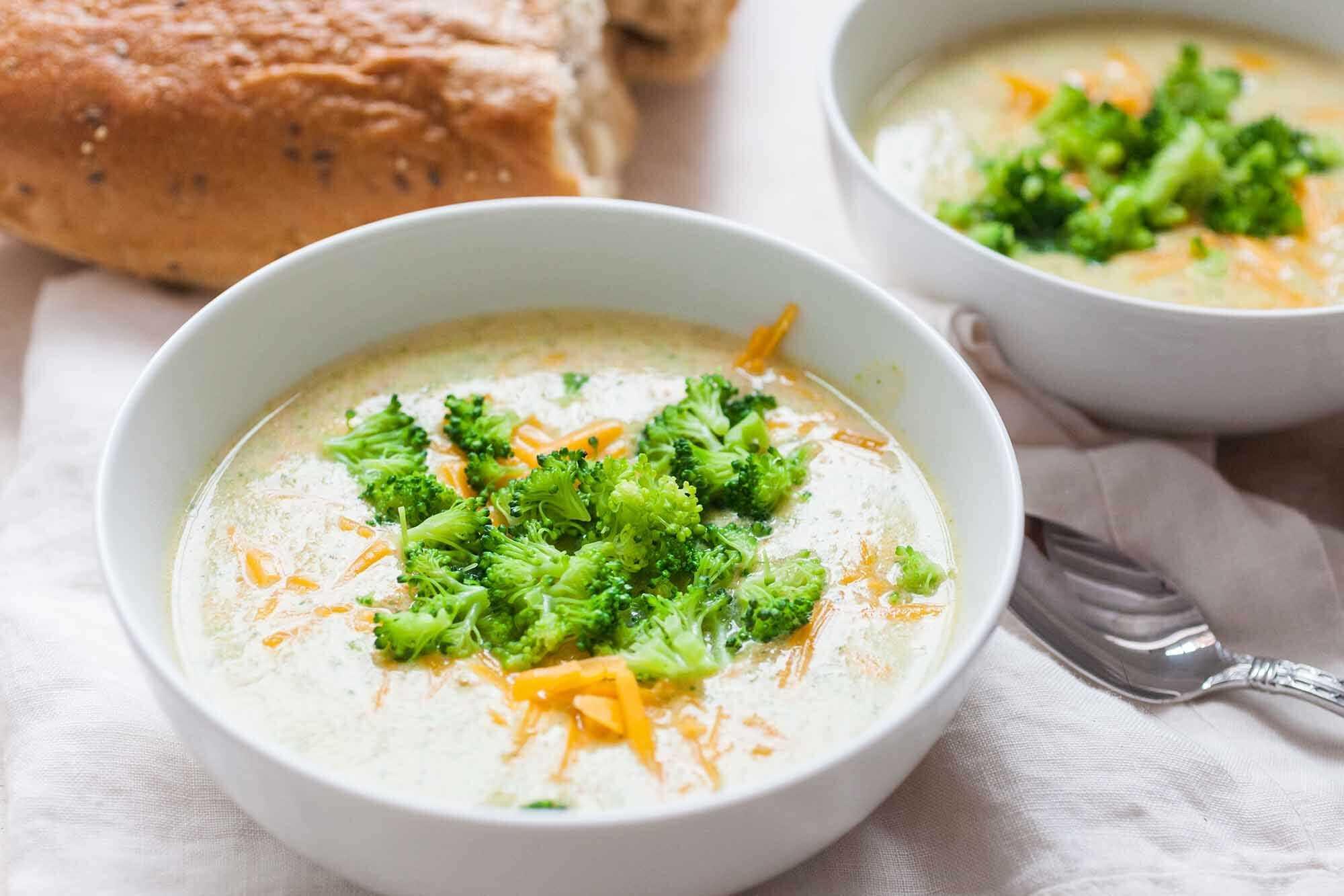 Sopa vegetariana de brócoli y queso cheddar dos cuencos y una cuchara