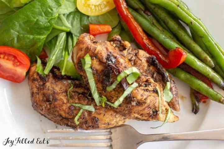 Cerca del pollo balsámico en un plato con ensalada y judías verdes