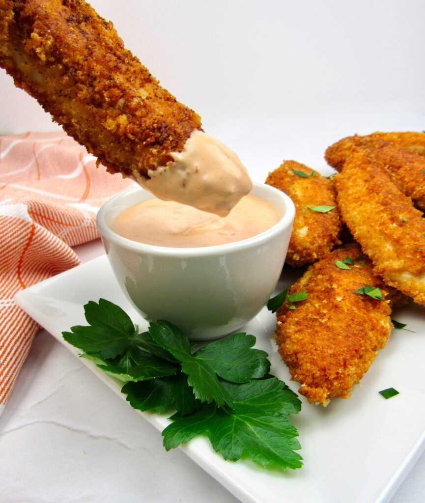 filetes de pollo en un plato blanco que se sumergen en salsa