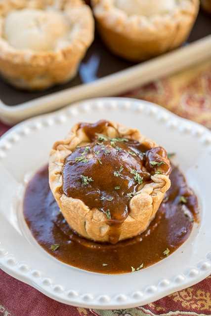 Mini Steak & Ale Pies - Guinness olla asada en masa de pastel horneada en un molde para muffins. Inspirado en nuestro viaje a Londres, Inglaterra. Estos saben mejor que cualquiera de los pasteles de carne que comimos en los pubs de Londres. ¡Mmm! Olla asada a fuego lento, corteza de pastel y salsa Guinness. ¡Puede adelantarse y congelarse para una comida rápida más tarde! #londres # pingüino # filete # carne