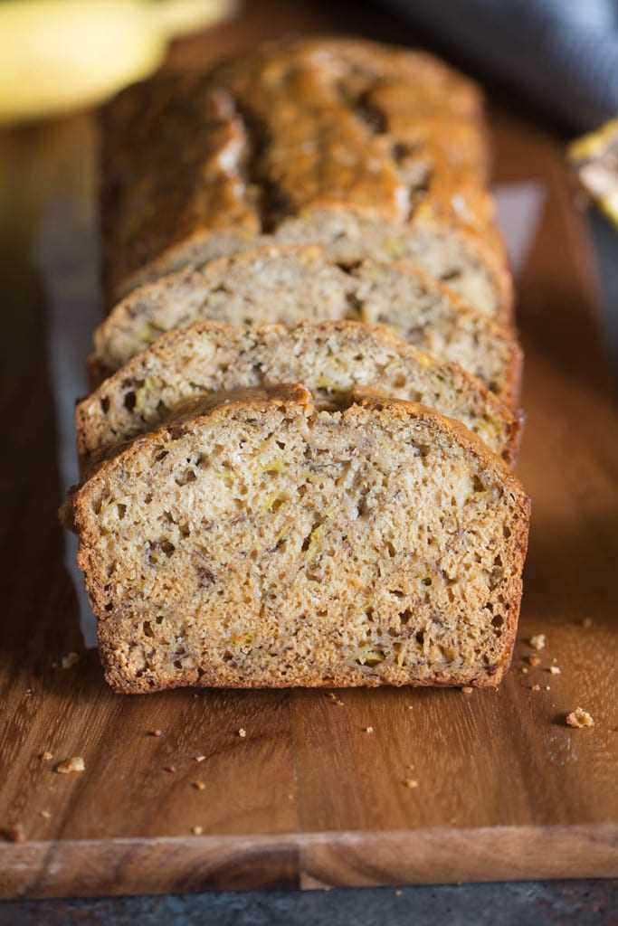 Varias rebanadas de Skinny Banana Bread apiladas contra el pan.