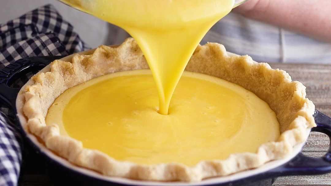 Verter el relleno de pastel de merengue de limón en una corteza de pastel precocida.