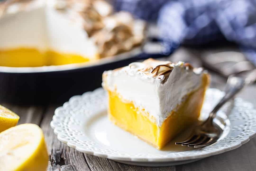Pastel de merengue de limón fácil servido en un plato con un paño azul a cuadros en el fondo.
