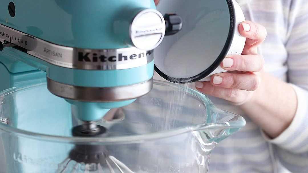 Agregar azúcar y maicena al merengue en un flujo lento y constante.