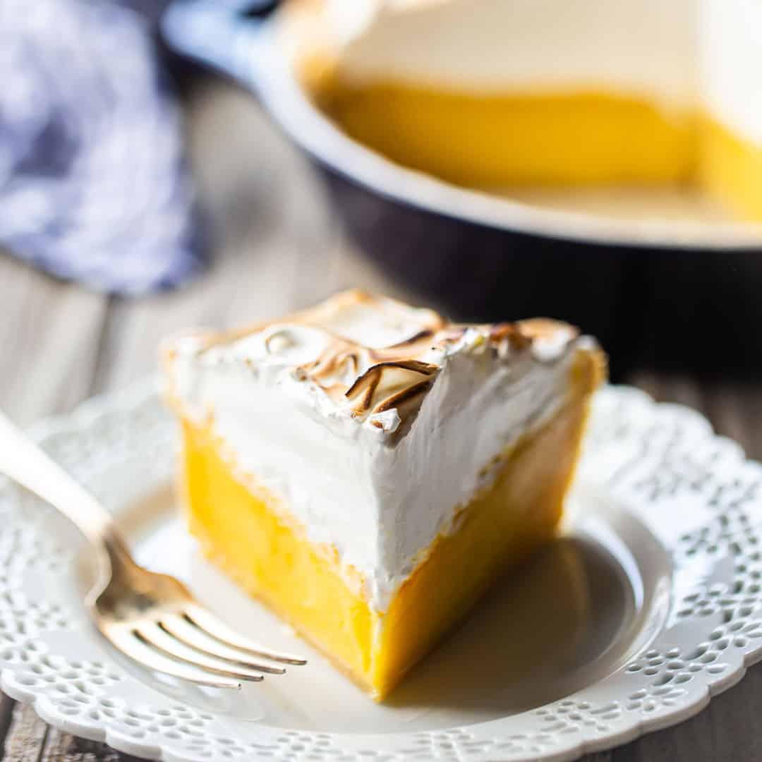 Pastel de merengue de limón en un plato blanco de encaje.