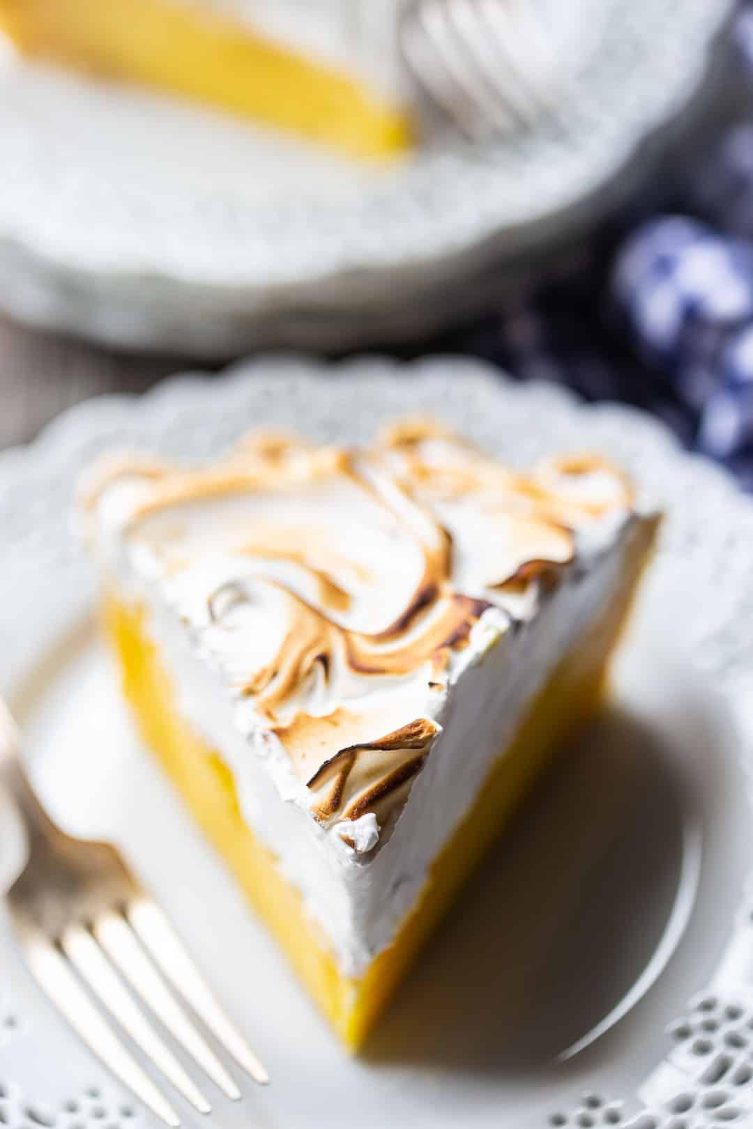 Rebanada de pastel de merengue de limón en un plato con un paño azul a cuadros.