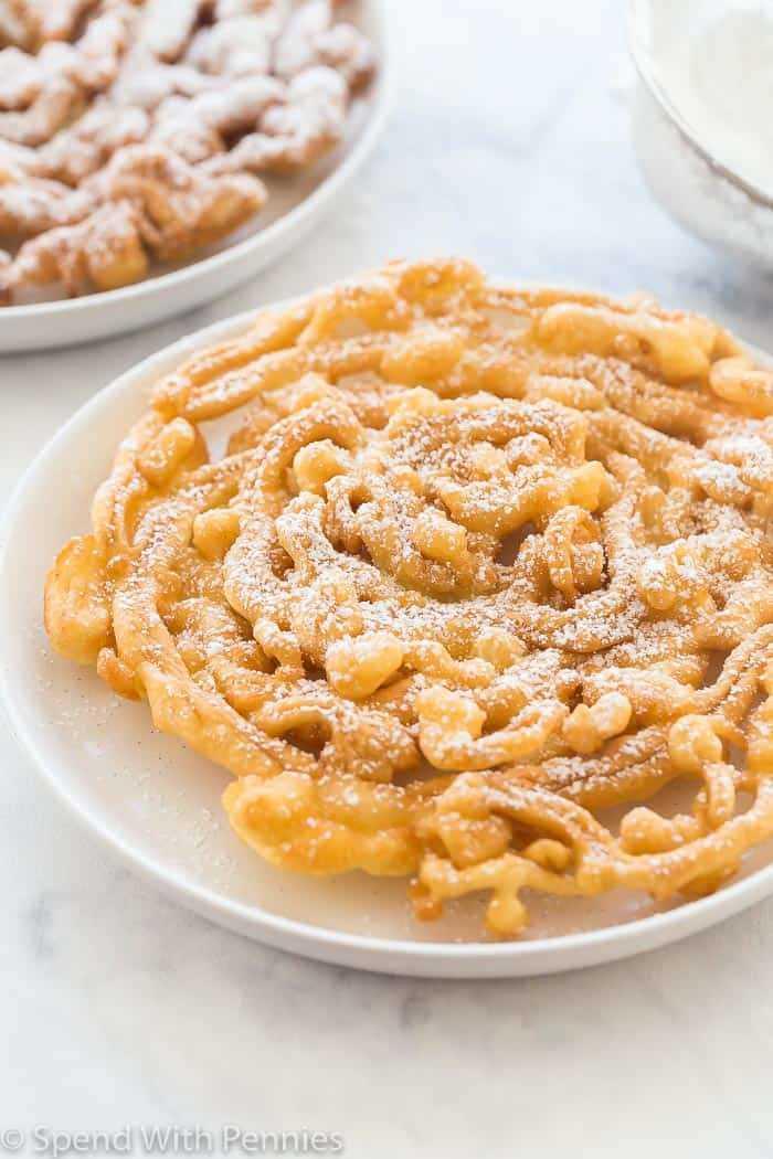 Un pastel de embudo cubierto con azúcar en polvo en un plato