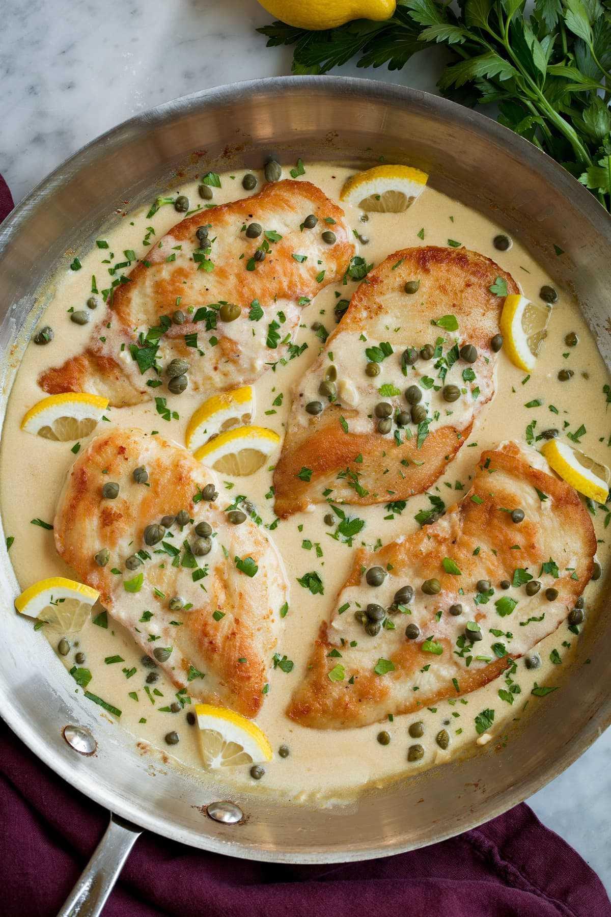 Cuatro porciones de piccata de pollo en salsa cremosa de piccata de limón, que se muestran después de cocinarlas en una sartén de aluminio grande.