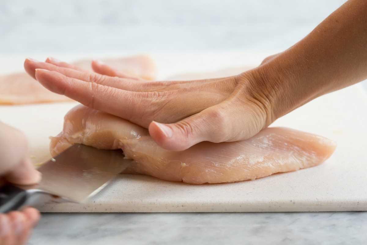 Mostrando cómo cortar una pechuga de pollo por la mitad para crear dos chuletas.