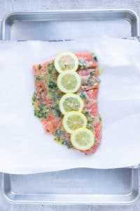 Rodajas de limón sobre el pescado en una bandeja para hornear.