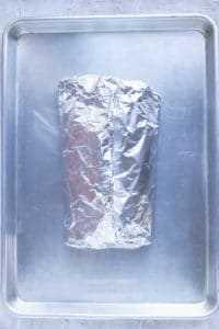 Salmón en un paquete de aluminio en una bandeja para hornear listo para agregar al horno.