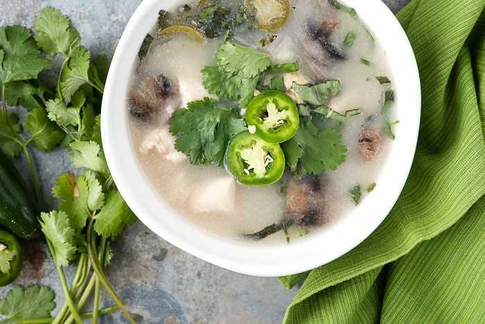 foto cenital de un tazón blanco lleno de sopa de coco y champiñones tailandeses con pollo lento, adornado con hierbas frescas y rodajas de jalapeño