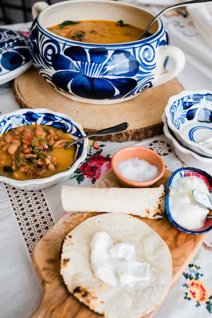 sopera y tazones para servir rellenos de frijoles pintos charros y una pila de tortillas de maíz untadas con crema agria