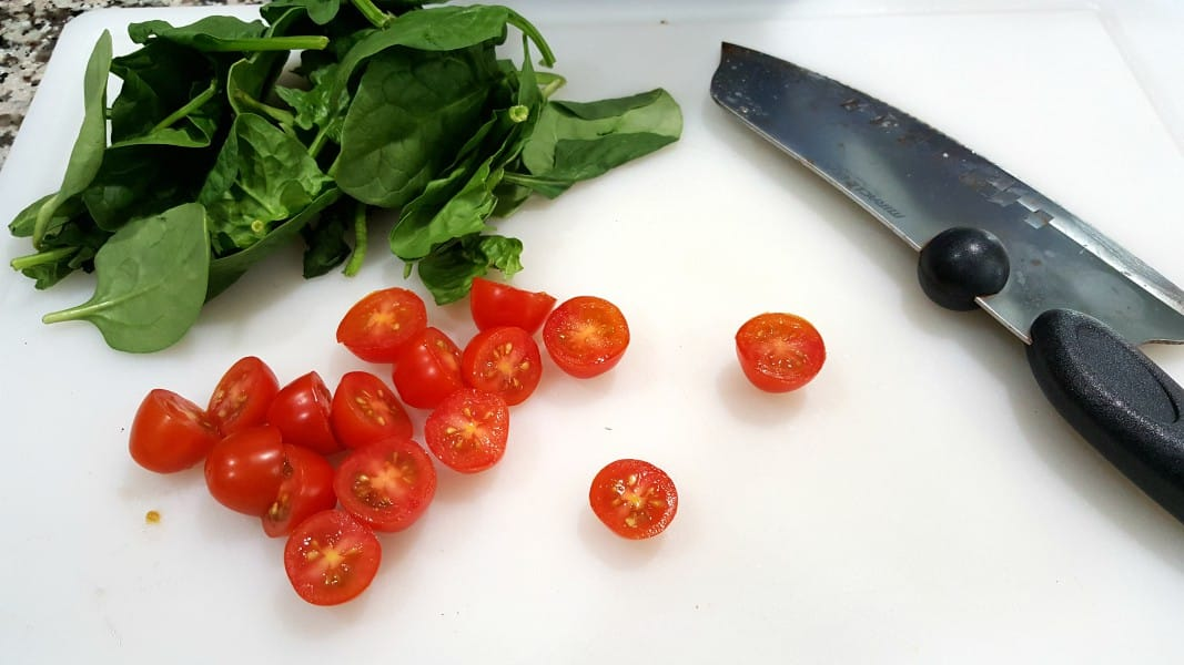 Tomates cherry cortados por la mitad con un cuchillo y un montón de espinacas baby