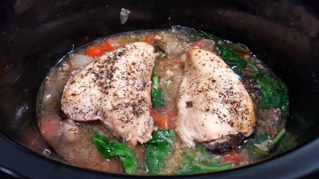 Pollo toscano e ingredientes en una olla de cocción lenta.