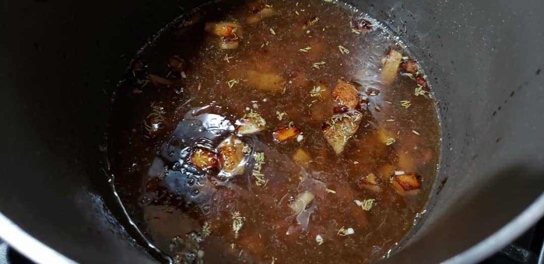 ajo, tomillo, caldo de res y salsa Worcestershire añadidos a los champiñones en una sartén