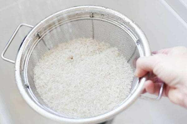 Arroz blanco enjuagado en un colador en el fregadero
