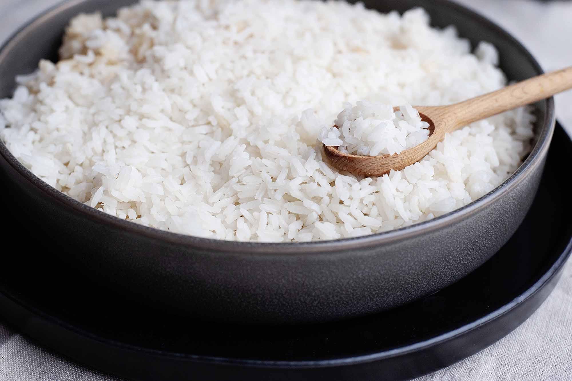 Perfecto arroz blanco en una sartén de metal con una cuchara de madera llena de arroz blanco cocido.