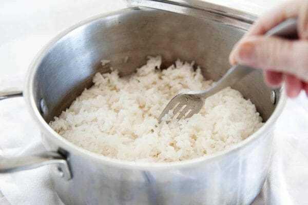Cacerola de plata con arroz blanco perfecto se esponja con un tenedor.